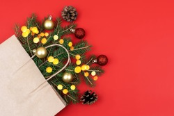 Festive Christmas composition with fir branches into craft package and christmas balls against red background and golden bokeh. Eco-friendly packaging in kraft paper. Flat lay, copy space, mock up