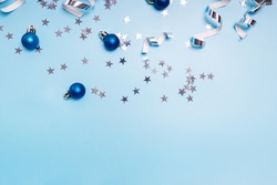 Festive Christmas decor on blue background. Star shapad confetti, swirls and baubles. Flat lay with copy space