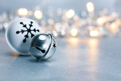 festive christmas jingle bells on grey background with blurred garland lights. macro view