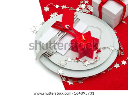 festive christmas table place setting decoration in red and silver. candle light dinner