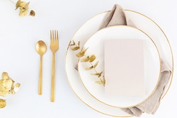 Festive christmas, wedding, birthday table setting with golden cutlery and porcelain plate. Blank card mockup. Restaurant menu template. Flat lay, top view