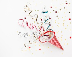 Festive composition with colorful confetti, Christmas ornaments and streamers on white. Celebration concept ideas for Christmas, New Year. Flat lay, copy space.