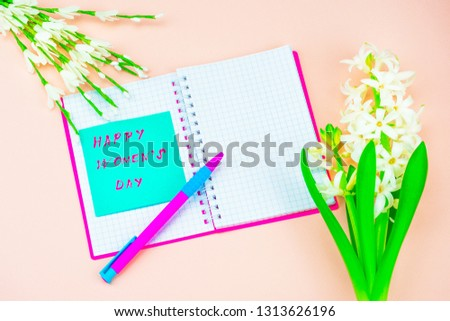 Festive concept. Congratulate on the International Women's Day. Notebook and pen, card with congratulations. Congratulations on March 8, spring background pink #1313626196