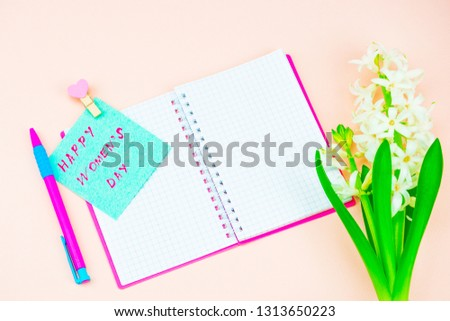 Festive concept. Congratulate on the International Women's Day. Notebook and pen, card with congratulations. Congratulations on March 8, spring background pink #1313650223