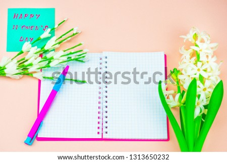 Festive concept. Congratulate on the International Women's Day. Notebook and pen, card with congratulations. Congratulations on March 8, spring background pink #1313650232