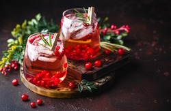 Festive Cranberry and rosemary cocktail with ice on the dark background. Alcoholic or non-alcoholic cocktail.