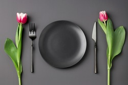 Festive creative black table setting with and tulip bouquet on dark background. Valentine's Day, Wedding Day, Birthday, Women's Day and Mother's Day. Flat lay