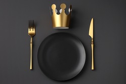 Festive creative royal table setting on a dark background. Gold crown, fork and knife. Valentine's Day, Wedding Day, Birthday, Women's Day and Mother's Day. Flat lay