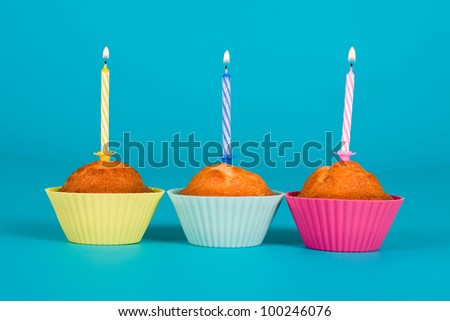 Festive cupcakes with a candles on gradient background