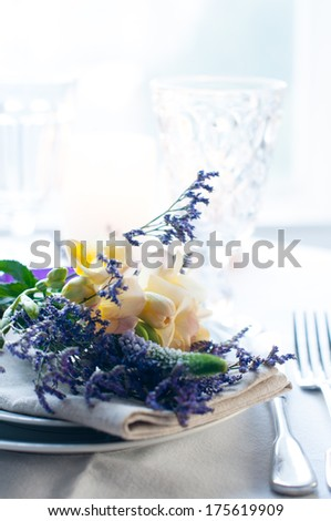 Festive dining table setting with a bouquet of yellow and purple freesias flowers, crockery and cutlery, on white background, daylight.