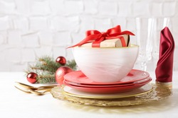 Festive dishware with gift and Christmas decorations on white table
