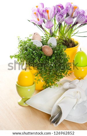 festive easter table setting with flowers, eggs and candles decoration on white background