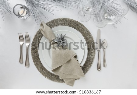 Festive formal fine dining Christmas or New Year's Eve holiday dinner party table setting place setting with white china plates, silverware, cloth napkin, wine glasses and silver glitter decorations #510836167