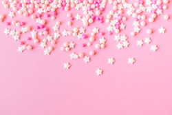 Festive frame made of colorful pastel sprinkles on a pink background, copy space on top. Sprinkle sugar with balls and stars, decoration for cake and bakery products. Top view or flat lay