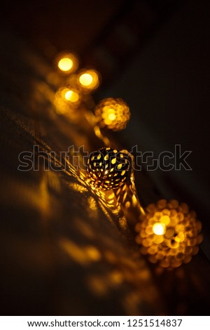 Festive garland carved metal bowl is lit from within with a Golden light. Bronze balls with slots-Christmas lights, creating a festive mood #1251514837