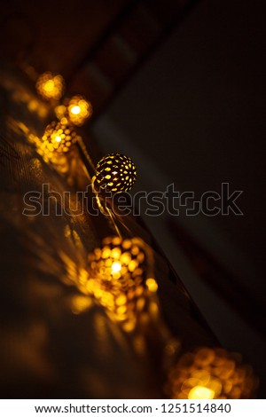 Festive garland carved metal bowl is lit from within with a Golden light. Bronze balls with slots-Christmas lights, creating a festive mood #1251514840