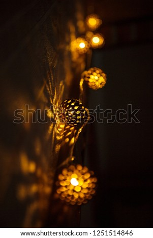 Festive garland carved metal bowl is lit from within with a Golden light. Bronze balls with slots-Christmas lights, creating a festive mood #1251514846