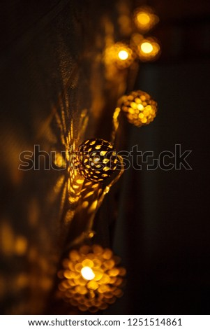 Festive garland carved metal bowl is lit from within with a Golden light. Bronze balls with slots-Christmas lights, creating a festive mood #1251514861