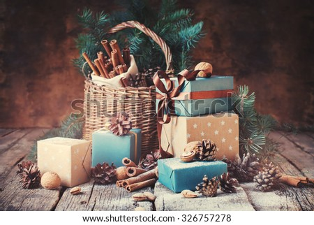 Festive Gifts with Boxes, Coniferous, Basket, Cinnamon, Pine Cones, Walnuts on Wooden Background. Christmas Presents Toned in Vintage Style
