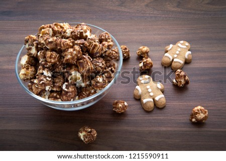 Festive Gingerbread Popcorn in bowl on wooden top with gingerbread men. #1215590911