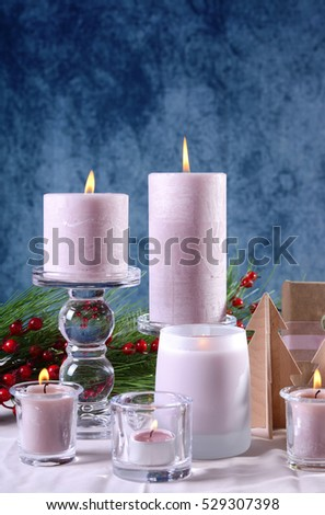 Festive glamorous holiday Christmas table setting with pink candles, gift against a blue background.
