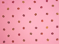 Festive glitter multicolored pattern. Pink background. Scattered golden, crimson and orange florets. Party template.