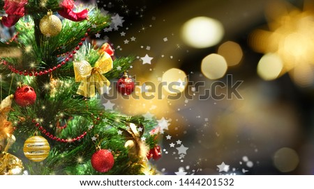 Festive green Christmas tree decorated with gold and red toys balls and bows with soft focus in evening and beautiful dark blurred defocused sparkling background with golden highlights, copy space. #1444201532