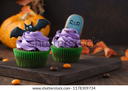 Festive Halloween cupcakes decorated with gingerbread cookies: tombstone and bat. Dark background with pumpkin and copy space, selective focus.