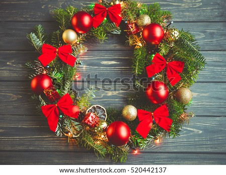 Festive handmade wreath from Christmas tree branches with red bows and  garland lights
