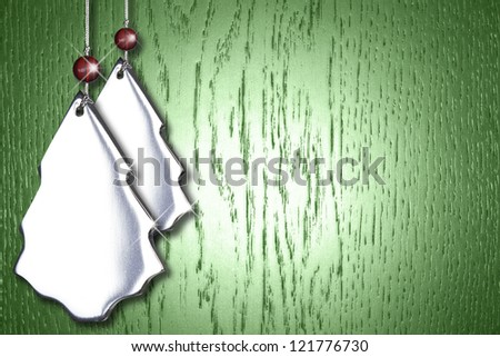 Festive holiday Christmas background with silver tree ornaments on wood.