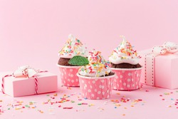 Festive holiday cupcakes for Birthday, Woman or Mothers Day. Pink paper decorations, sweet chocolate cupcakes with sprinkles and gift boxes on pink background. Party time concept.