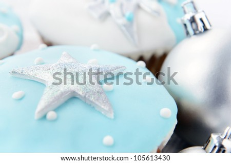 Festive holiday frosty icy white christmas theme cupcakes with silver ornament baubles