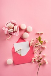 Festive holiday greeting card for Valentines, Birthday, Woman, Mothers Day. Rose macaroons in gift box, Cherry blossoms, empty envelope. Sweet macarons present on pink background. Top view, copy space