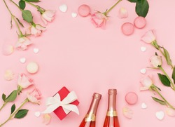 Festive holiday greeting card for Valentines, Birthday, Woman or Mothers Day. Flowers, bottle of wine, sweets and gift on pink background. Valentines day concept. Flat lay, top view, copy space.