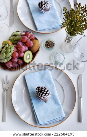 Festive holiday table setting with pine cones as decoration for a simple minimalist theme