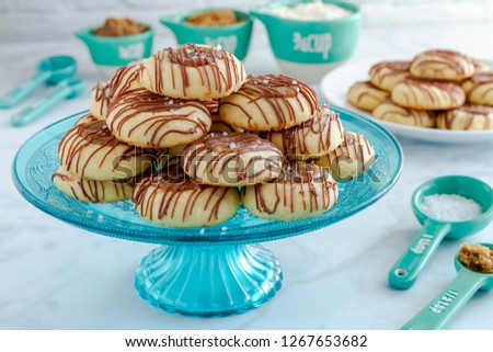 Festive kitchen counter with salted caramel thumprint cookies drizzled with chocolate surrounded by ingredients in blue and white cooking utensils