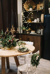 Festive kitchen in Christmas decorations. Christmas dining room. Beautiful New Year decorated classic home interior. New Year and Christmas background