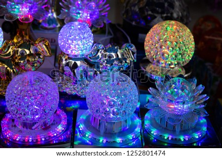festive led lights of different shapes glow in the dark. ball-shaped and flower-shaped lamps are sold at a holiday sale.