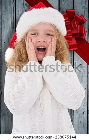 Festive little girl with hands on face against wood with festive bow