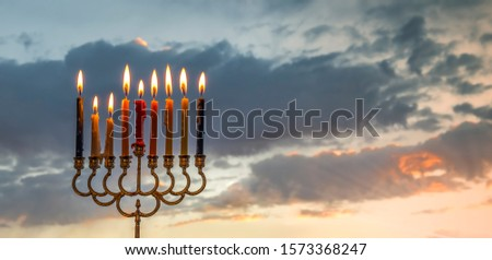 Festive menorah with lights of burning  candles is traditional symbol of Hanukkah Holiday. Blurred background with morning clouds and sunbeams #1573368247