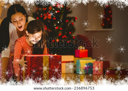 Festive mother and daughter opening a glowing christmas gift against fir tree forest and snowflakes