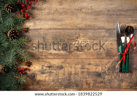 festive New Year Christmas dinner concept. Christmas decorations and Cutlery on a dark rustic table. Christmas table place setting. Winter holidays background. Top view, flat lay, copy space