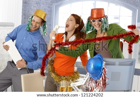 Festive new year office party, office workers having fun with accessories.