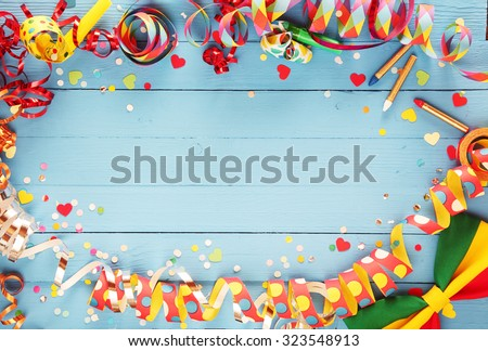 Festive party border or frame of colorful spiral streamers and confetti arranged on a rustic old blue wooden background with a bow tie in the corner and copyspace