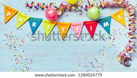 Festive Party Time banner with copy space and a border of colorful triangular bunting , streamers and balloons around blue wood with confetti Foto stock ©
