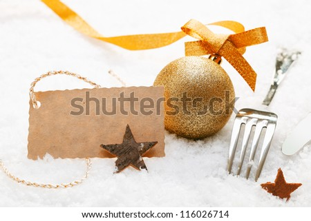 Festive place setting with Christmas decorations and silver cutlery in fresh winter snow with a decorative blank gift tag