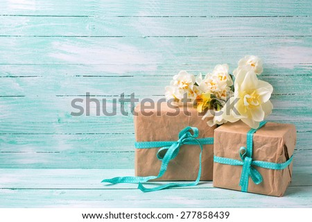 Festive present boxes  and flowers  on turquoise painted wooden background. Place for text. Selective focus.