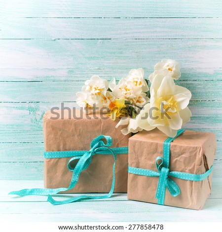 Festive present boxes  and flowers  on turquoise painted wooden background. Place for text. Selective focus. Square image.