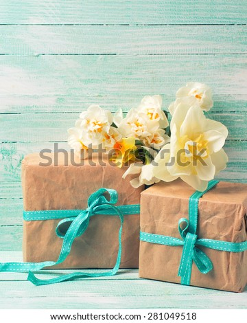 Festive present boxes  and flowers  on turquoise painted wooden background. Place for text. Selective focus. Vertical, toned image.