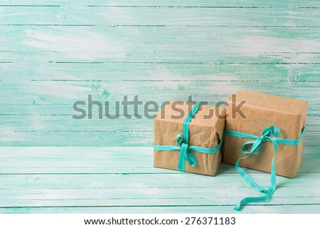 Festive present boxes with ribbon on turquoise painted wooden background. Place for text. Selective focus. #276371183